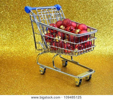 Mini Shopping Cart With Red Decorative Christmas Balls And Golden Glitter Background