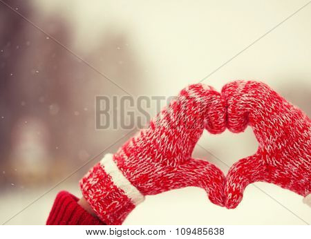 Heart of mittens in snow. Red knitted gloves in winter