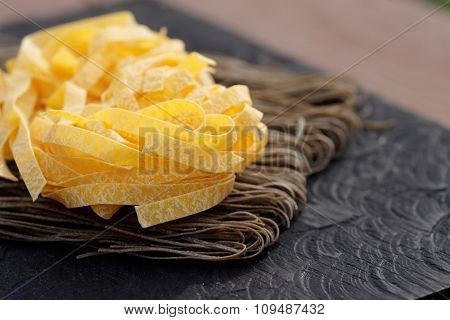 Two types of pasta on wooden plank, outdoor shot