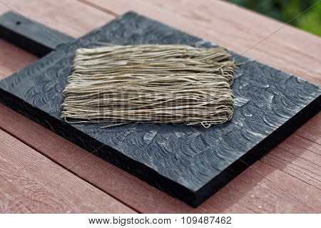 Squid ink pasta on wooden cutting board