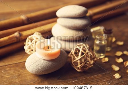 Decorated composition with candles, pebbles and bamboo on wooden background, close up