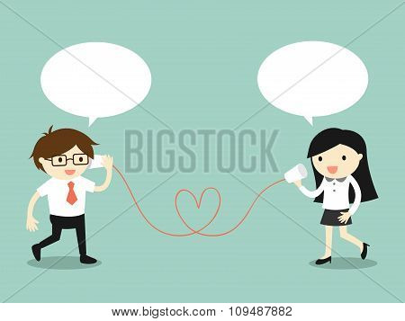Love in office. Businessman and business woman talking via cup telephone.
