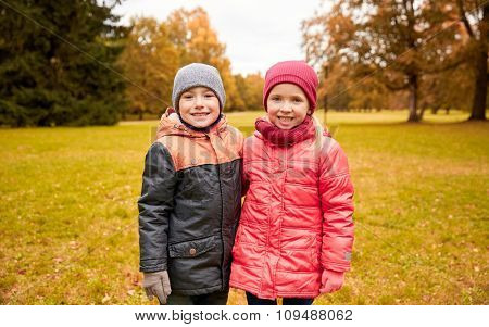 childhood, leisure, friendship and people concept - happy little girl and boy in autumn park