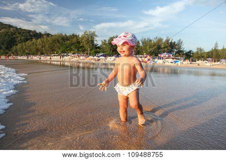Happy child comes into the sea.