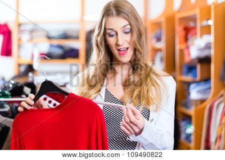 Woman shopping in boutique or fashion store choosing clothes