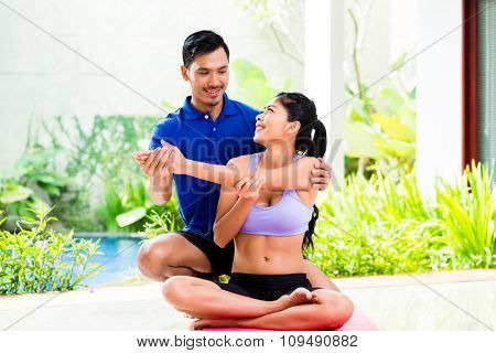 Asian fitness trainer exercising sport with woman
