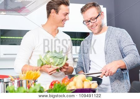 Friends cooking vegetables and meat in domestic kitchen