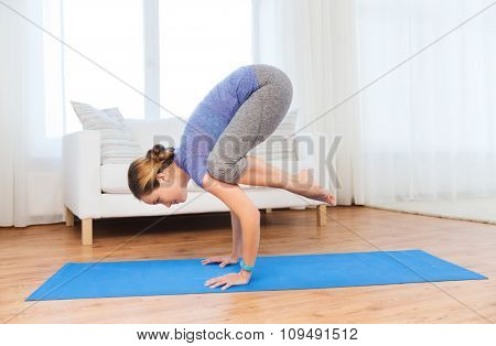 fitness, sport, people and healthy lifestyle concept - woman making yoga in crane pose on mat