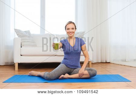 fitness, sport, people, diet and healthy lifestyle concept - happy woman with cup of smoothie sitting on mat at home