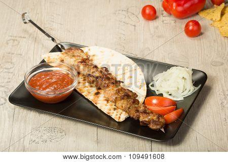 shashlik. kebab skewer, black rectangular plate. sauce and onions
