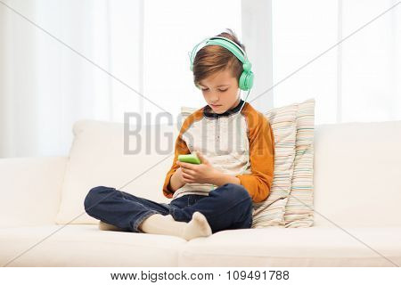 leisure, children, technology and people concept - boy with smartphone and headphones listening to music or playing game at home