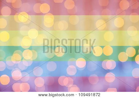 holidays, gay pride, homosexuality and tolerance concept - blurred golden lights over rainbow flag background