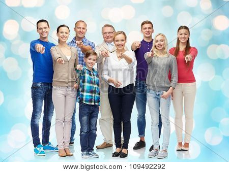 family, gender, generation and gesture concept - group of happy people pointing finger on you over blue holidays lights background