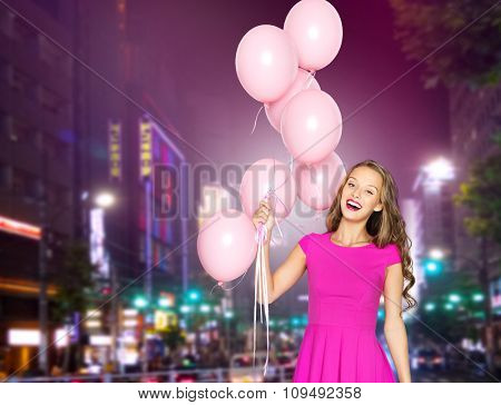 people, holidays, party, nightlife and fashion concept - happy young woman or teen girl in pink dress with helium air balloons over night city street background