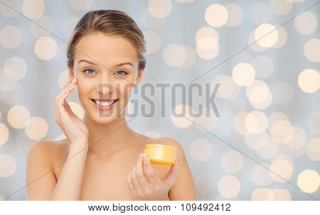 beauty, people, cosmetics, skincare and cosmetics concept - happy young woman applying cream to her face over holidays lights background