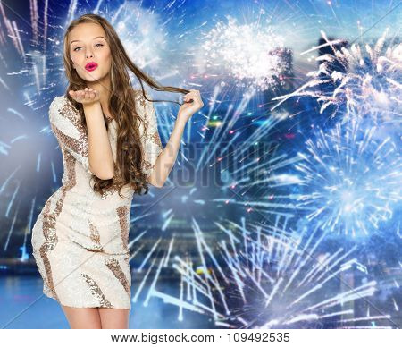 people, style, holidays, hairstyle and fashion concept - happy young woman or teen girl in fancy dress with sequins and long wavy hair sending blow kiss over firework at night city background