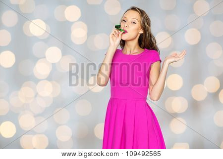 people, holidays and celebration concept - happy young woman or teen girl in pink dress and party cap over lights background