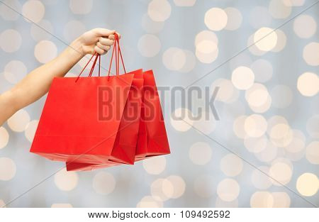 people, sale, consumerism, advertisement and commerce concept - close up of hand holding red blank shopping bags over holidays lights background