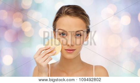 beauty, people and skincare concept - young woman cleaning face with exfoliating sponge over purple holidays lights background