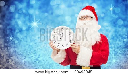 christmas, holidays, time and people concept - man in costume of santa claus with clock showing twelve over blue glitter or lights background