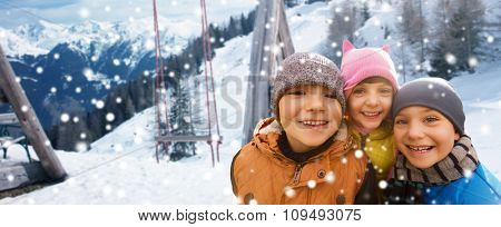 childhood, friendship, winter holidays, vacation and people concept - group of happy kids hugging over swing and snowy mountains background