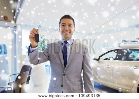 auto business, car sale, consumerism and people concept - happy man showing key at auto show or salon over snow effect