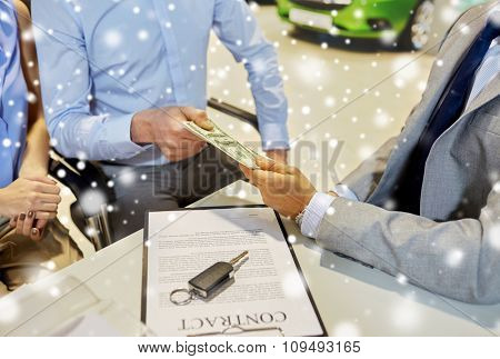 auto business, sale and people concept - close up of customers giving money to dealer and buying car in auto show or salon over snow effect