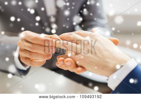 people, homosexuality, same-sex marriage and love concept - close up of happy male gay couple hands putting wedding ring on over snow effect