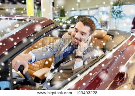 auto business, car sale, consumerism, technology and people concept - happy man sitting in car and calling on smartphone at auto show or salon over snow effect