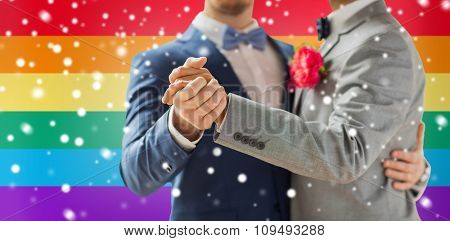 people, homosexuality, same-sex marriage and love concept - close up of happy male gay couple holding hands and dancing on wedding over rainbow flag background and snow effect