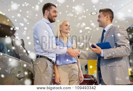 auto business, car sale, technology, gesture and people concept - happy couple with car dealer shaking hands in auto show or salon over snow effect