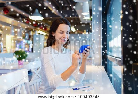 business, people, technology and lifestyle concept - smiling young woman texting message with smartphone at cafe over snow effect