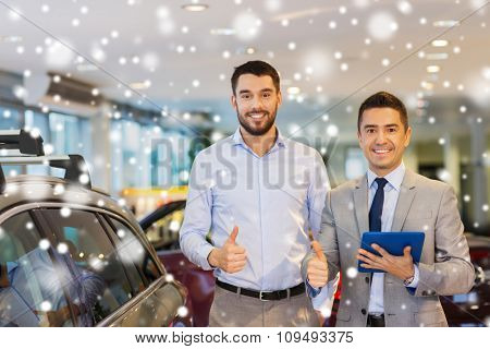 auto business, car sale, technology, gesture and people concept - happy man and car dealer with tablet pc computer showing thumbs up in auto show or salon over snow effect