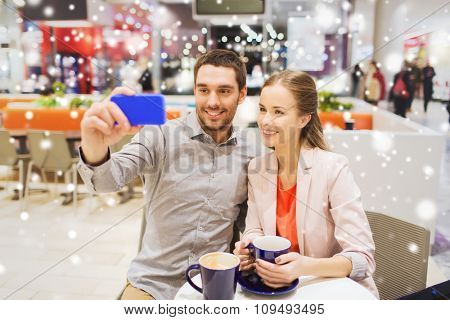 sale, shopping, consumerism, technology and people concept - happy young couple with smartphone taking selfie at cafe in mall with snow effect