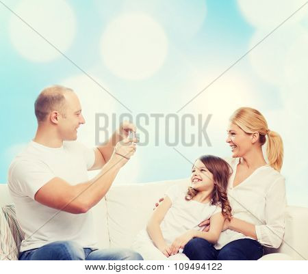 family, holidays, technology and people concept - smiling mother, father and little girl with camera over blue lights background