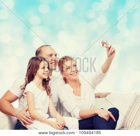 family, holidays, technology and people concept - smiling mother, father and little girl making selfie with camera over blue lights background