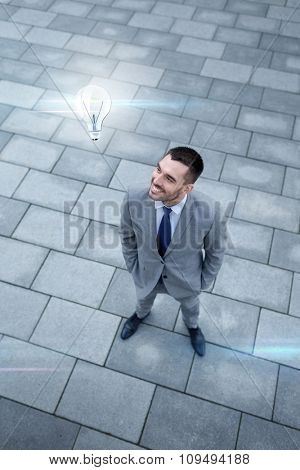business, development, idea, energy and people concept - young smiling businessman with lightning bulb image outdoors from top
