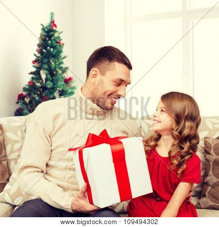 family, holidays and people concept -smiling father and daughter with gift box over living room and christmas tree background