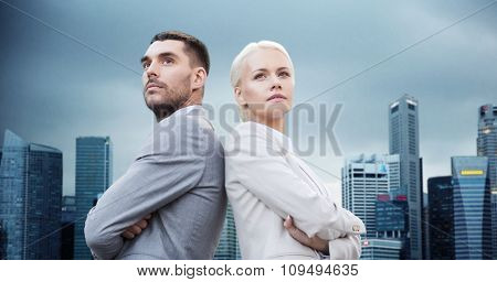 business, partnership, teamwork and people concept - businessman and businesswoman standing over city buildings background