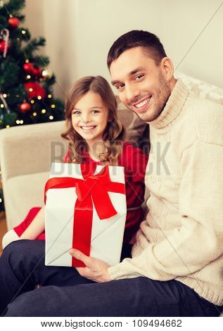 christmas, x-mas, winter, happiness and people concept - smiling father and daughter holding gift box