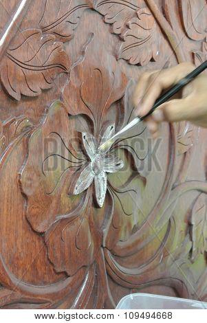 Skilled craftsman adding gold leaf skin to the wood carving