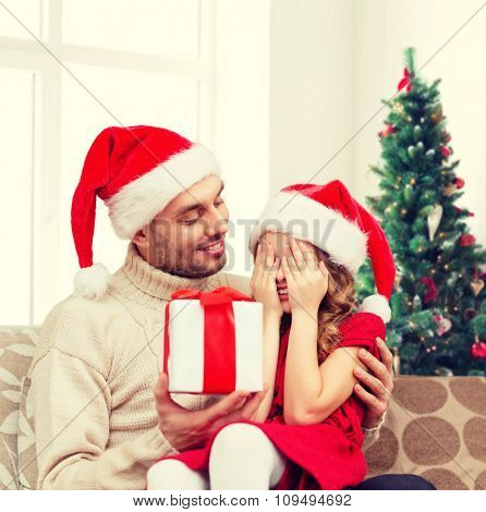 family, winter holidays and people concept - smiling daughter with closed eyes waiting for present from father over living room and christmas tree background
