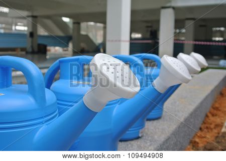 Row of portable watering cans or watering pot made from polymer