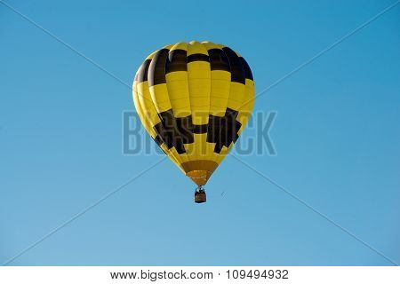 Black And Yellow Hot Air Balloon In A Blue Sky