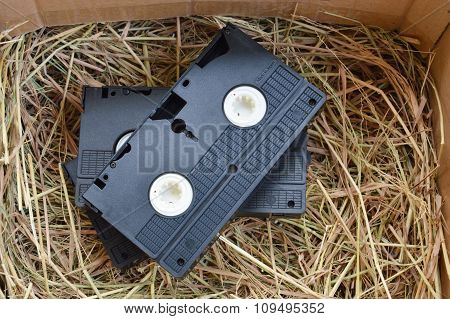 video recorder cassette on straw in paper box