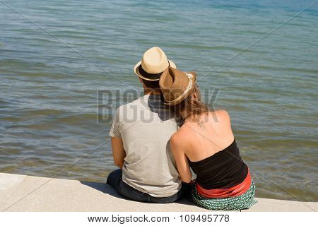 Pair Of Lovers Sitting At The Water's Edge
