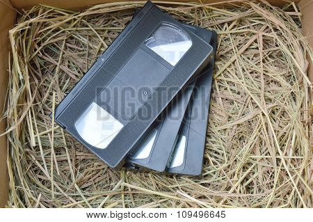 video recorder cassette on dry straw in box