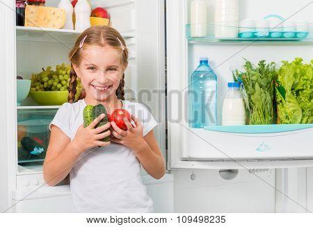 little smiling girl holding vegetables near fridge