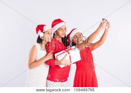 three indian girls with santa hat and gift box, posing for selfie with mobile, cheerful pose, close