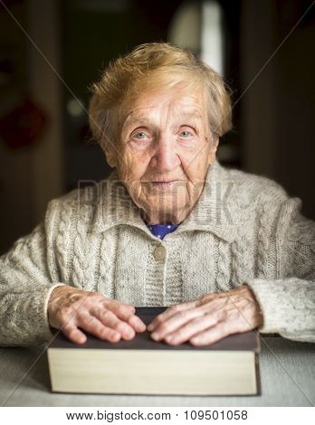 Elderly woman sitting at the table with his hands on the big book.